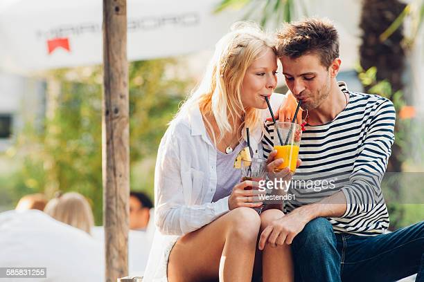 Young couple drinking fruit juice together at outdoor cafe