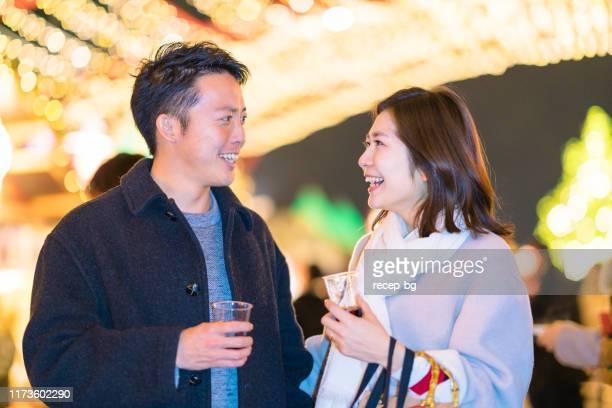 若いカップルは温めたワインを飲み、クリスマスマーケットを楽しんでいます - 向かい合わせ ストックフォトと画像