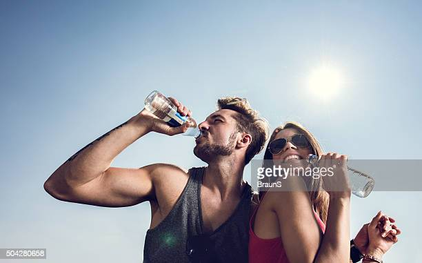 Young couple drinking water against the clear sky.