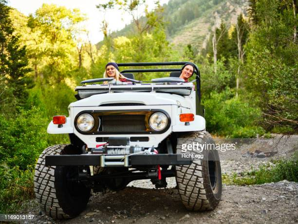 young couple driving an off road 4x4 - jeep stock pictures, royalty-free photos & images