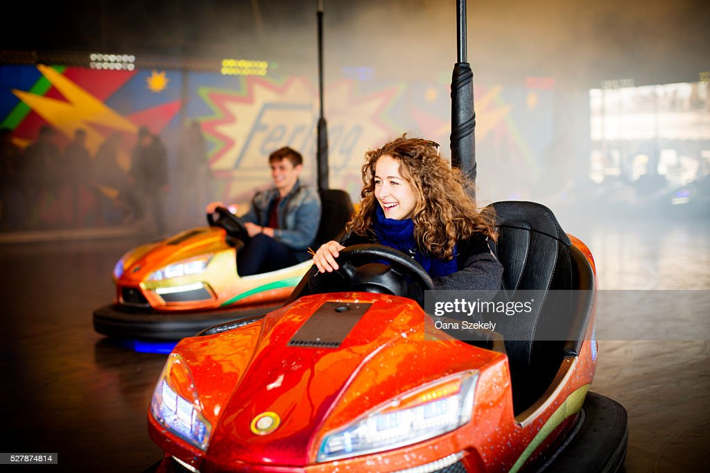 Young Couple Driving Bumper Cars In Amusement Park Stock Photo