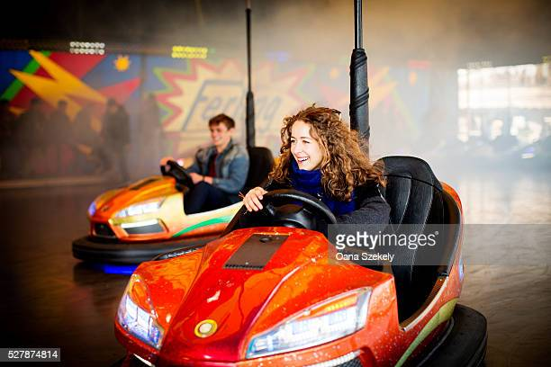 Young couple driving bumper cars in amusement park
