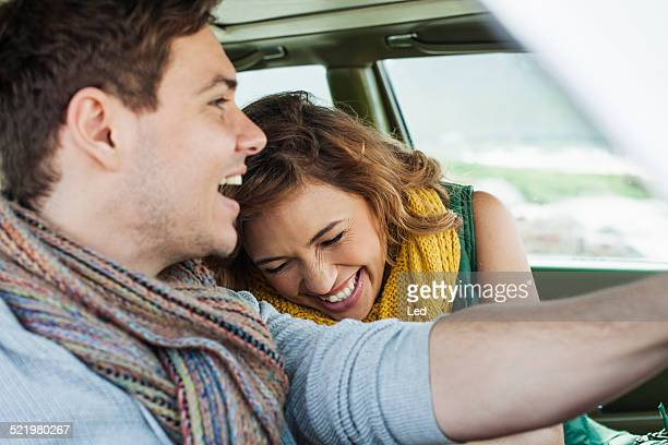 Young couple driving car laughing, Cape Town, Western Cape, South Africa