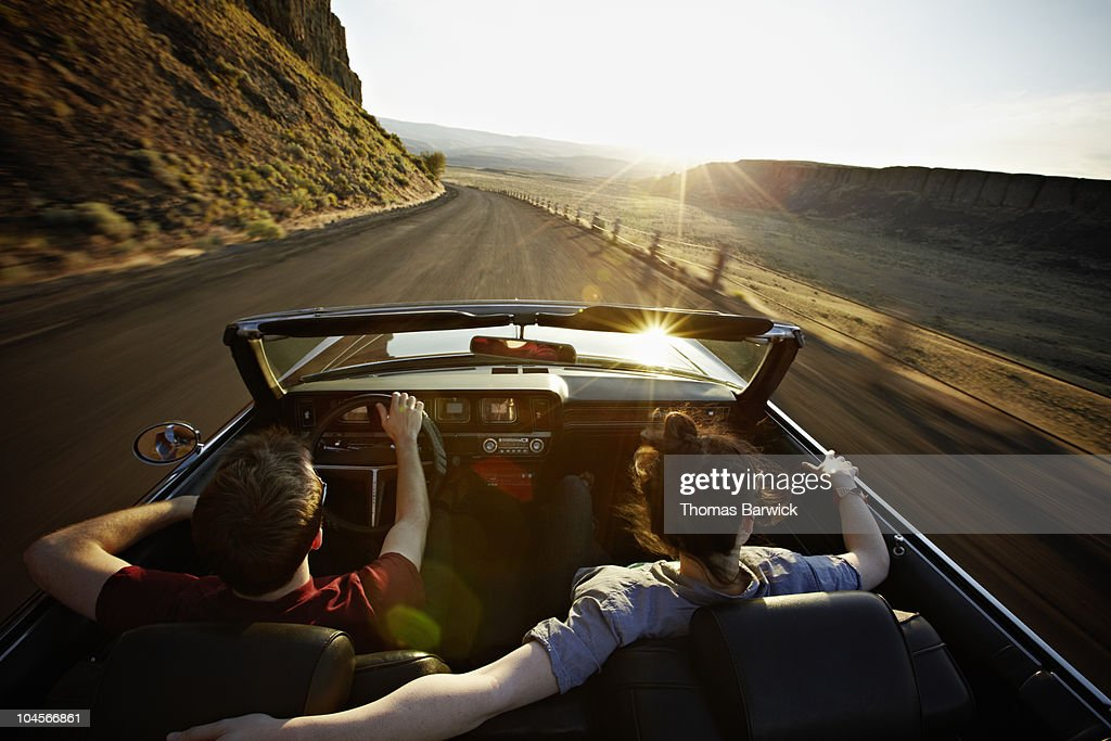 Young couple driving convertible at sunset : Stockfoto