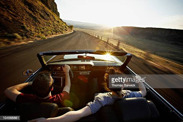 young couple driving convertible at sunset - driver stock pictures, royalty-free photos & images