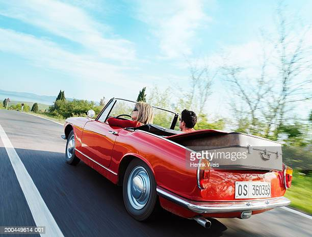 young couple driving convertible car in countryside, rear view - convertible stock pictures, royalty-free photos & images
