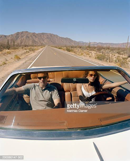 Young couple driving convertible, close-up