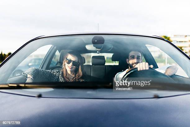young couple driving in a car - frontaal stockfoto's en -beelden