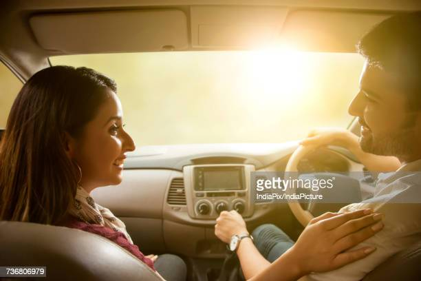 young couple driving in car - front passenger seat stock photos and pictures