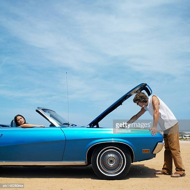 young couple driving in convertible car hood raised