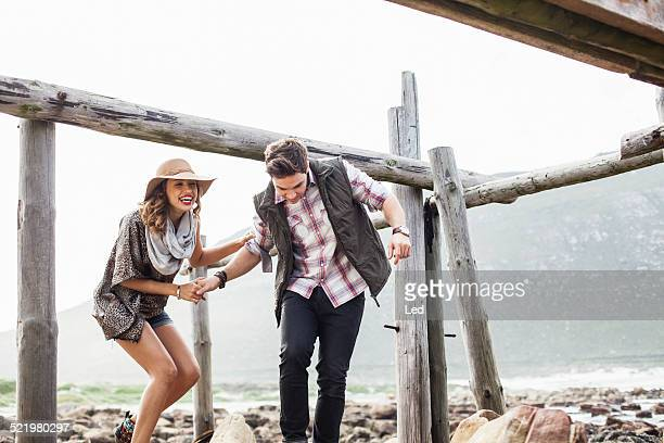 young couple ducking under old pier, cape town, western cape, south africa - ducking stock pictures, royalty-free photos & images