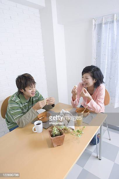 Young couple eating at table