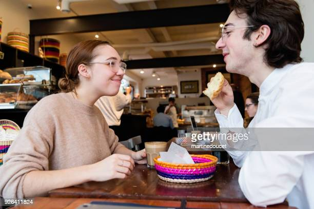 """young couple eating breakfast in a local coffee shop. - """"martine doucet"""" or martinedoucet stock pictures, royalty-free photos & images"""
