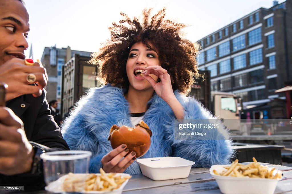 Young couple eating burger and chips outdoors : Stock Photo