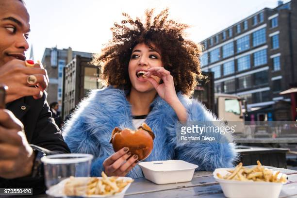 young couple eating burger and chips outdoors - eten stockfoto's en -beelden