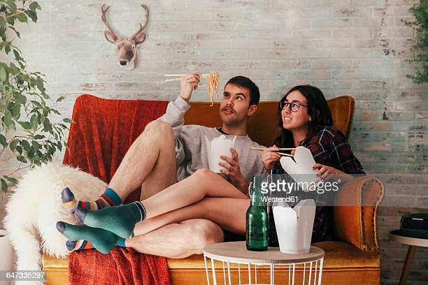 young couple eating chinese take-away food at home - take away food stock pictures, royalty-free photos & images