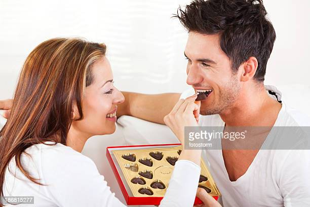 Young couple eating chocolate candies