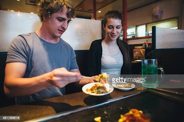 Young couple eating exotic food in self service restaurant