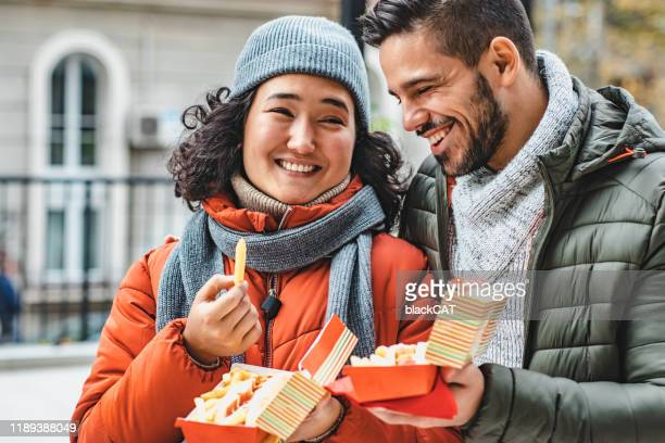 young couple eating fast food and walking - fast food french fries stock pictures, royalty-free photos & images