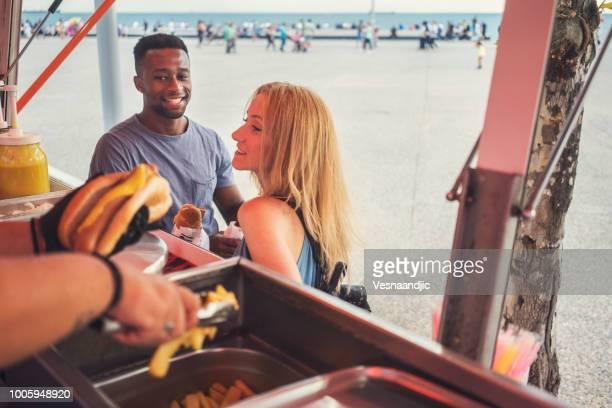 Junges Paar Essen vor Imbisswagen