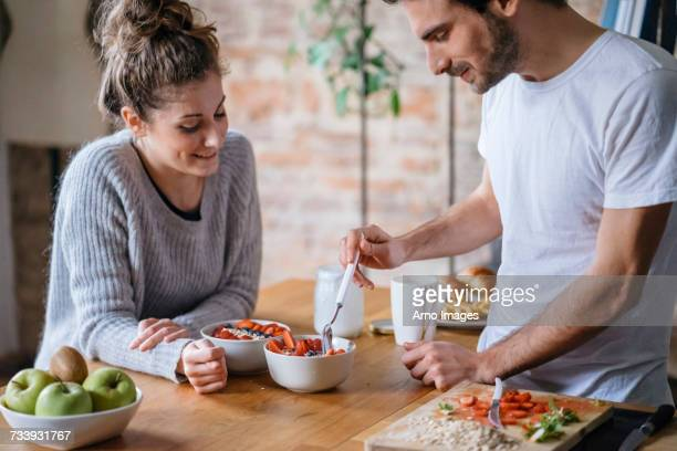 young couple eating fruit breakfast at kitchen counter - man eating woman out stock photos and pictures