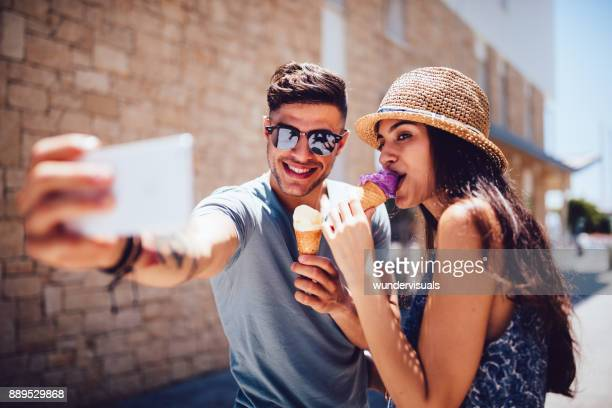 Young couple eating ice-cream and taking selfies on summer holidays