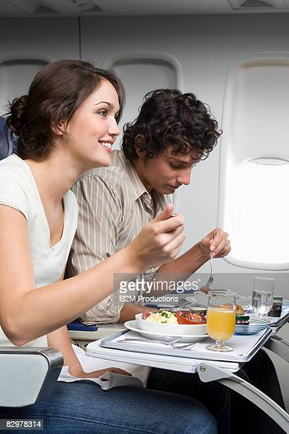 Young couple eating in airplane