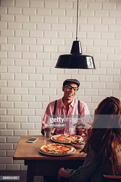 Young couple eating pizza in restaurant