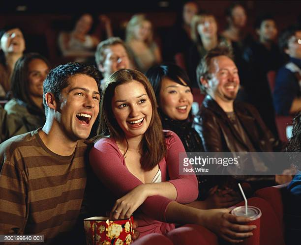 Young couple eating popcorn in cinema, laughing, close-up