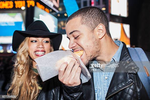 Young couple eating street food