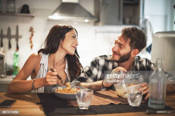 young couple eating together at home - evening meal stock pictures, royalty-free photos & images