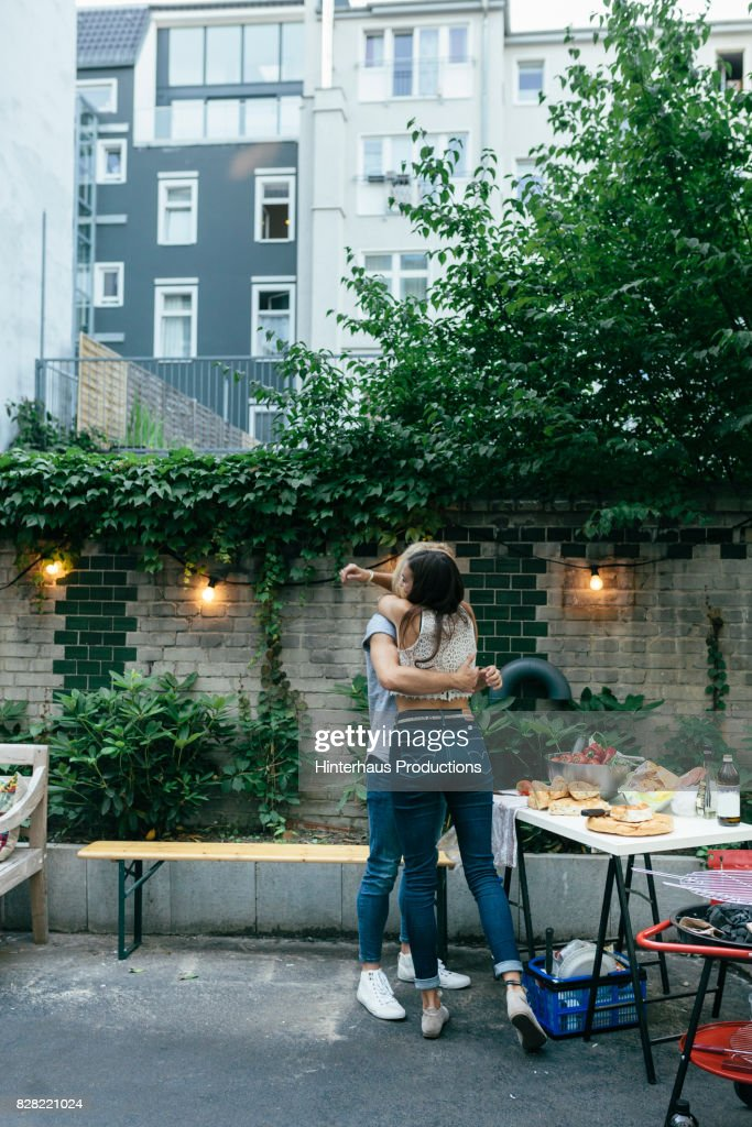 Uberlegen Young Couple Embrace While They Prepare For A Barbecue
