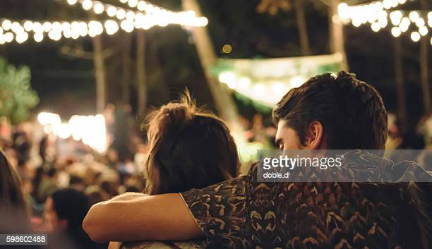 Young couple embracing and enjoying in night music festival