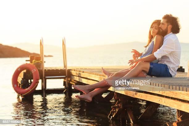 Junges Paar umarmt und sitzen am pier