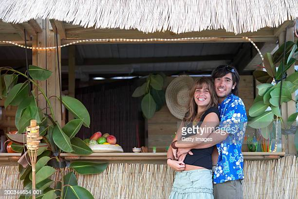 Young couple embracing at beach bar, smiling, portrait