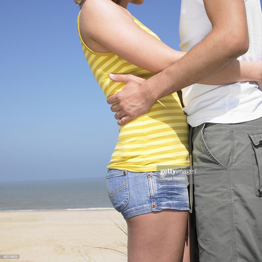 Young couple embracing at beach. : Stock Photo