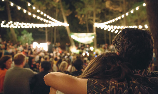 Young couple embracing at night music festival - gettyimageskorea
