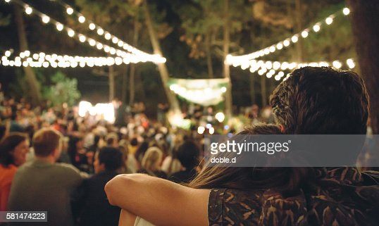 Young couple embracing at night music festival