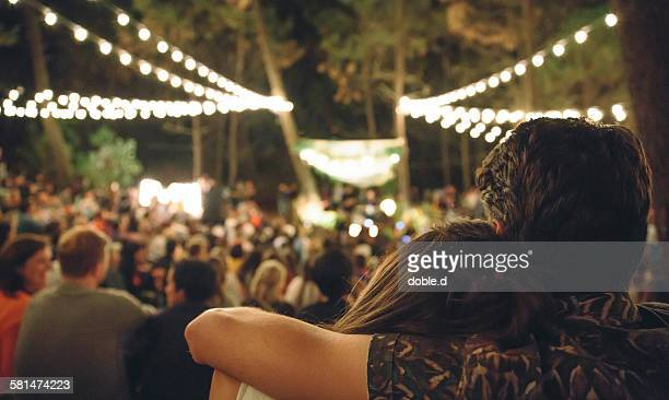 young couple embracing at night music festival - concert photos et images de collection