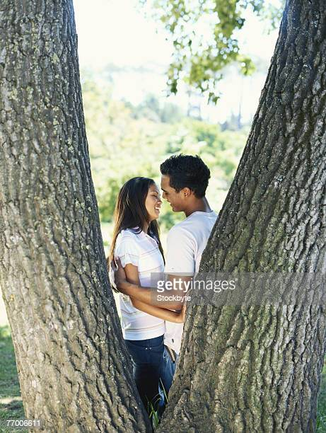 Young couple embracing behind tree