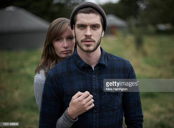 young couple embracing during glamping holiday. - serious stock pictures, royalty-free photos & images