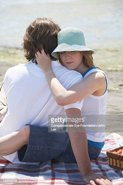 young couple embracing during picnic at seashore - compassionate eye foundation stock pictures, royalty-free photos & images