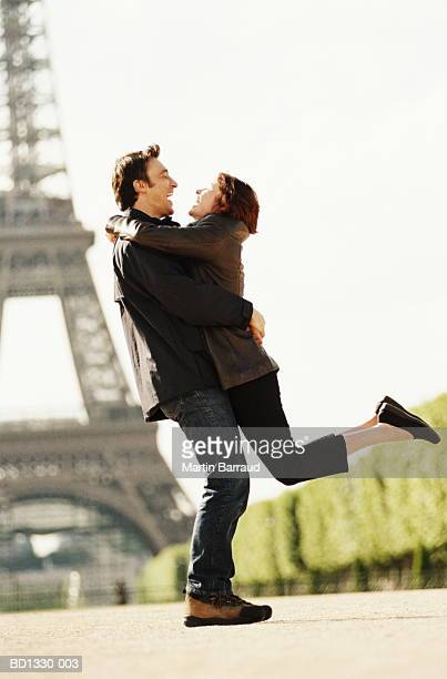 Young couple embracing, Eiffel Tower in background, Paris, France