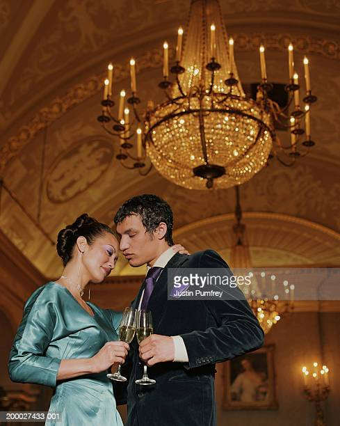 young couple embracing, holding glasses of champagne - 舞踏会 ストックフォトと画像
