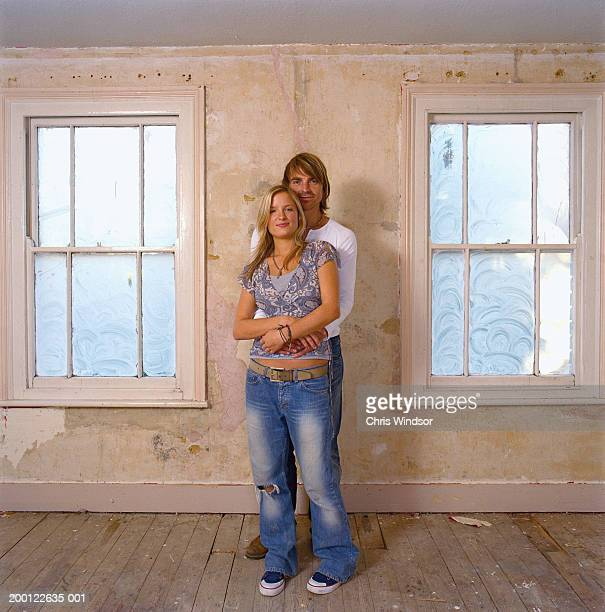 young couple embracing in bare room, portrait - heteroseksueel koppel stockfoto's en -beelden