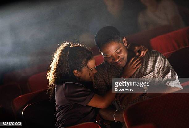Young couple embracing in cinema