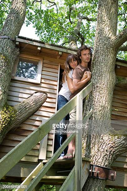 Young couple embracing in doorway of tree house, low angle view