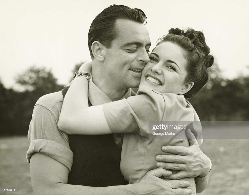 Young couple embracing in field, man kissing woman, (B&W) : Stock Photo