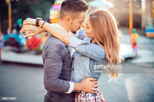 Jeune couple embrassant dans le luna park.