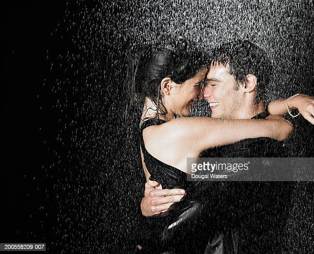 Young couple embracing in rain at night, side view